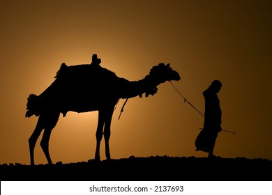 A silhoutte of a dromedary and bedouin