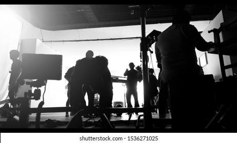 Silhouette Bilder von Videoproduktion und Beleuchtung Set für die Filmen, welches Team von Film-Crew arbeitet und Silhouette Schatten von Kamera und professionelle Ausrüstung in großen Studio für kommerzielle Werbung.