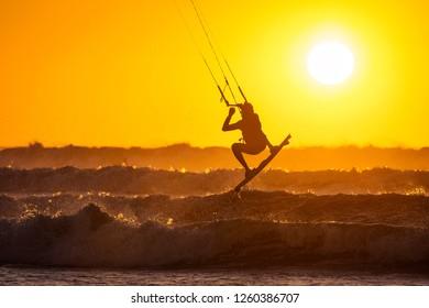 Silhoutte of kitesurfers enjoying big waves at sunset in Essaouira, Morocco. Beautiful landscape in background