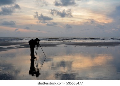 silhoutte of a lone photograper by the beach at sunrise
