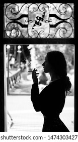 Silhoutte of long haired curly beautiful girl. With cigarete .Smoking.Black and white.
