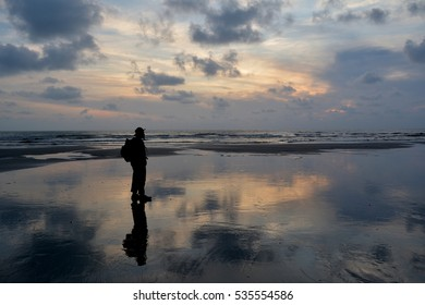 silhoutte of a man with bagpack on a beach at sunrise