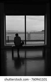 Silhoutte of a man sitting alone on bench through the window