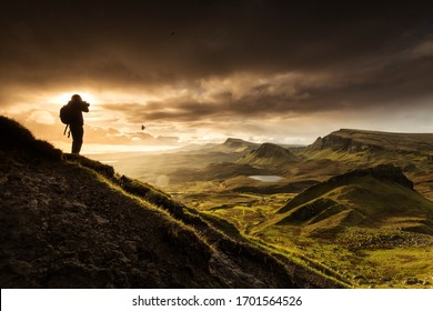 Silhoutte of photographer shooting scenic view of Quiraing mountains in Isle of Skye, Scottish highlands, United Kingdom. Sunrise time with colourful an rayini clouds in background