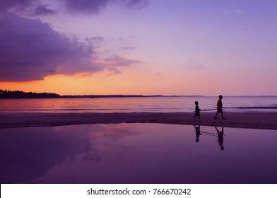 silhoutte of two local kids at Trikora Beach, Bintan, Indonesia