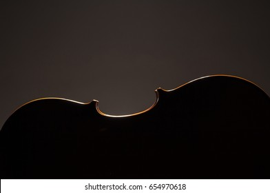 silhoutte of violoncello, cello with dark and warm background