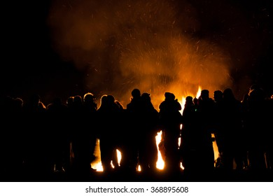 silhouttes of people watching a bonfire,sparks and smoke behind them