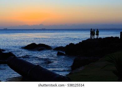 Silhuet of people watching the sunset at Porto da Barra Bahia Brazil