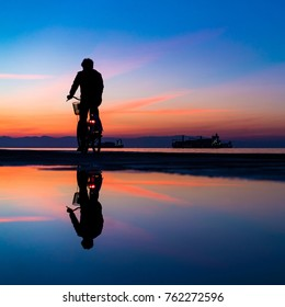 Silhuette of Man on Bicycle and his reflection on water from rain, against Lovely Colors Sky