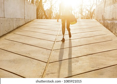 Silhuette of sunlit athletic disabled girl with prosthetic leg in sportswear walking outdoor in urban area