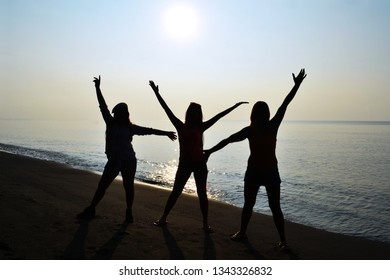 Silhuette of three ladies having fun with sunrise on the beach