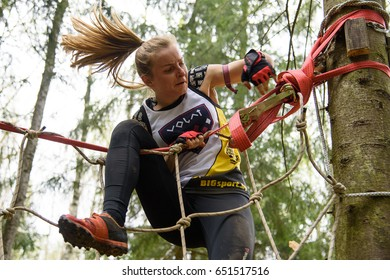 SILICHI/BELARUS – MAY 7, 2017: A lady surmounts vertical net obstacle during Bison Race, an obstacles course race, held on May 7 in Silichi, Belarus.