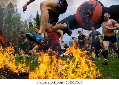SILICHI/BELARUS – MAY 7, 2017: A participant of an extreme race jumps over fire during start of Bison Race, an obstacles course race, held on May 7 in Silichi, Belarus.