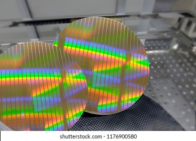 Silicon wafers being prepared for production as part of a manufacturing process a silicon wafers reflecting colors, semiconductors, blurred background