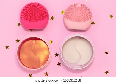 Silicone facial cleansing brushes with cleansing brush for massaging skin care and hydrogel cosmetic eye patch on pink background with golden stars. Flat lay, top view.