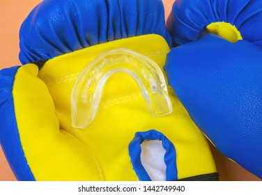 Silicone mouth guard on training boxing gloves. Close-up, selective focus.