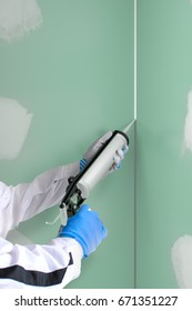 Silicone sealant cartridge with silicone gun fills the joint between two gypsum plasterboard's drywall