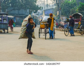 Siliguri, West Bengal/India – January 30 2012: Young Indian girl carrying a bag with a load on the street.