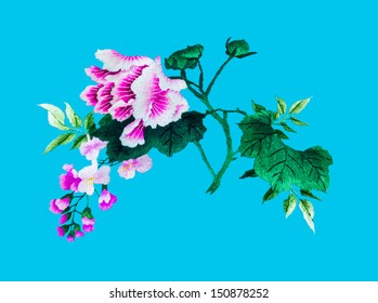 Silk flower sewing by hand on blue background.