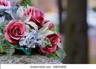 Silk flowers on a gravestone, soft focus