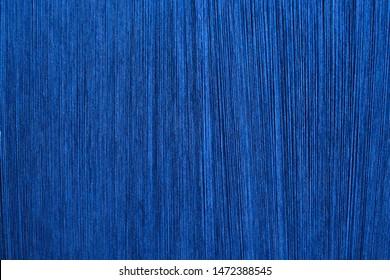 ฺBlue silk on a warping loom of a textile mill, Silk for weaving on a hand loom, Hand Made Silk Process, Close up macro detail of Yarn thread lines running in the weaving loom machine.
