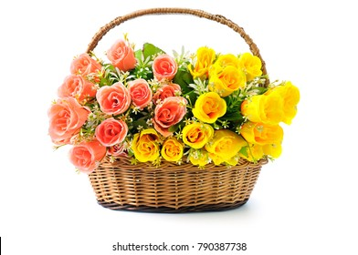 Silk red and yellow flowers in basket isolated on white background.