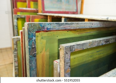 Silk screen printing screens stored in a wooden rack ready for printing.