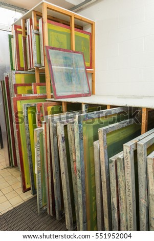 a60ba1e7 Silk screen printing screens stored in a wooden rack ready for printing.