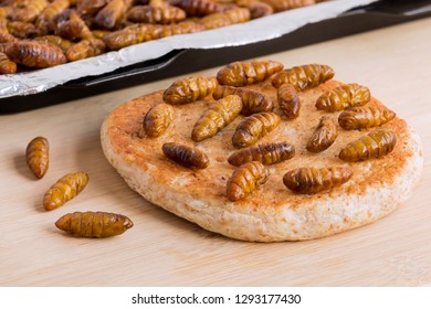Silkworm Pupae (Bombyx Mori). Food insects for eating as food. Bakery baked bread made of cooked insect meat with baking tray on wood background is good source of protein edible. Entomophagy concept.