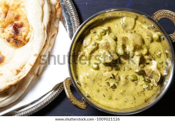 Silky Methi Khumb Matar malai curry or Creamy Fenugreek Mushroom peas curry on wooden background.