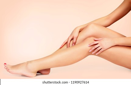 Silky smooth skin of female legs after depilation. Woman touches her legs by hands
