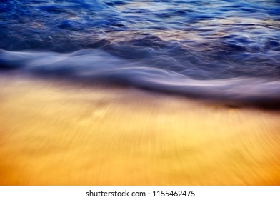 Silky smooth waves crashing on shore with sunset reflection along Barefoot Beach, Florida