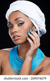 Silky touch. Beautiful African woman wearing a headscarf and touching her skin while looking at camera and standing against black background