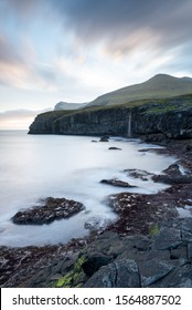 Silky white waves glide over the darkened red rocks and seaweed as a waterfall cascades down a mountain into the Atlantic Ocean, a promising sunrise lights up a moody skyline and cloud set overhead.