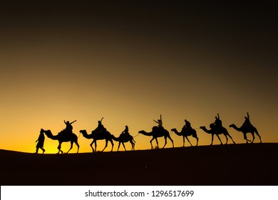 Sillhouette of camel caravan with happy peopple going through the desert at sunset with red sky in background