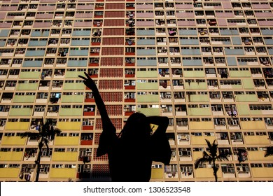 Sillhouette of girl posing in front of masion apartaments