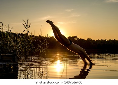 sillhouette of man dives into the water of lake at sunset