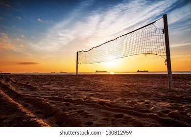 Sillhouette of a volleyball net and sunrise on the beach