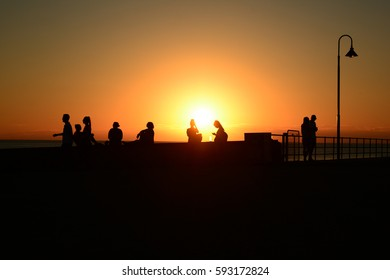 sillhouettes of people enjoying sunset at the beach