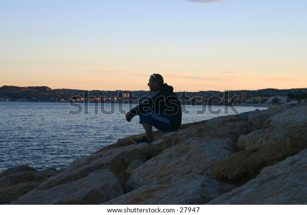 Sillouete of man alone on the rocks looking out to sea in Calpe southern Spain