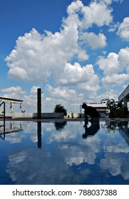 Sillouette of man working by the rooftop pool during a beautiful afternoon