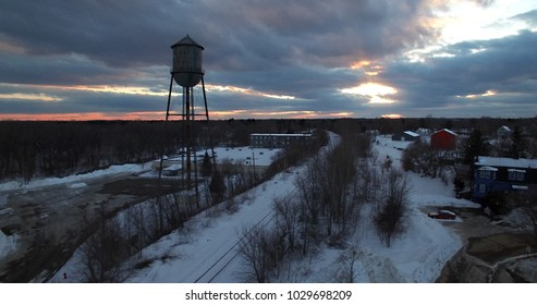 sillouette of water tower and sunset - rays shining through clouds
