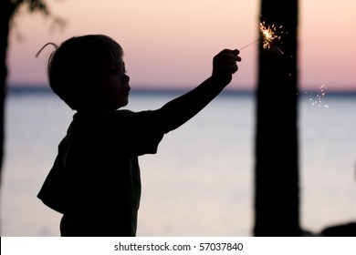 A sillouhette of a young boy holding a sparkler.