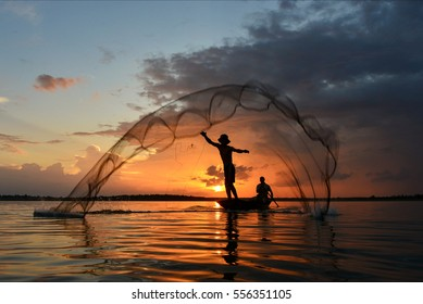 The silluate fisherman trowing the nets  on boat in river  at during sunrise,Thailand