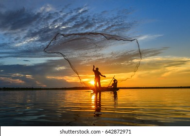 Silluate fisherman trowing the nets on during sunset,during sunrise,Thailand