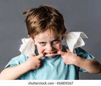 silly 5-year old red hair kid making a grimace with his big mouth, not listening with tissue in both ears for confronting misbehavior, contrast effects on grey background