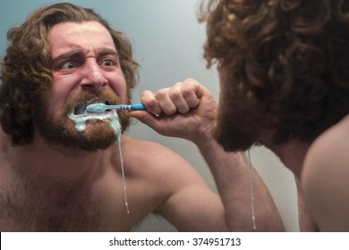 Silly bearded man brushing teeth in bathroom mirror