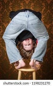 Silly boy upside down on a stool
