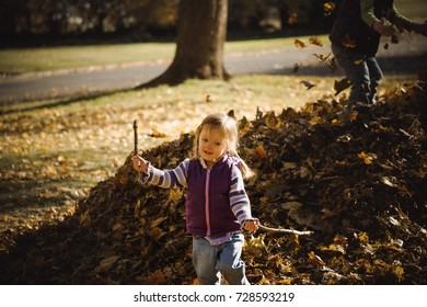 Silly child playing with sticks near a pile of fallen leaves