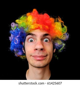A silly crazy man wearing a clown wig with rainbow colors